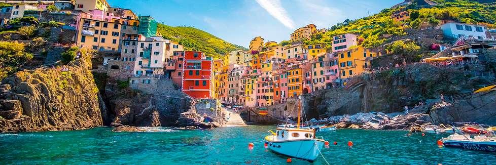 Blick vom Wasser auf ein buntes Fischerörtchen in Italien. Im Vordergund sieht man ein Fischerboot.